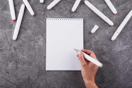 Female hands with a marker. Draw in a white notebook. Space for design. Top view.