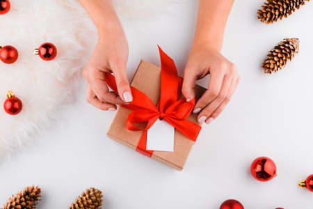 Gift wrapping. Packaging modern christmas present boxes in stylish gray paper with satin red ribbon. Top view of hands on white table with decoration 写真素材