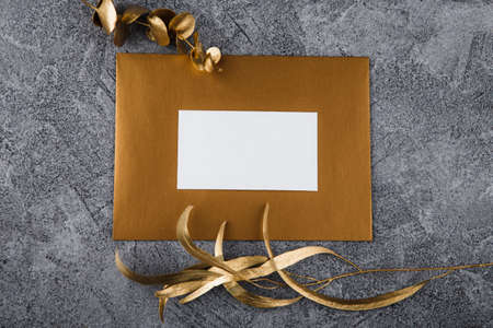Mockup white greeting card and envelope with golden fern leaves and light background. 写真素材
