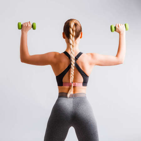 Beautiful young woman doing exercises with dumbbells. Photo athletic woman with perfect body on white background. Strength and motivation