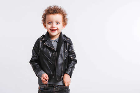 Little curly boy in black leather jacket on a light gray background. Rocker style Space for text.
