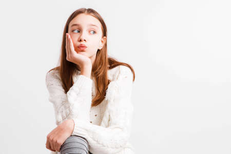 Emotional teen girl in a white knitted sweater on a light gray background.Space for text. 写真素材