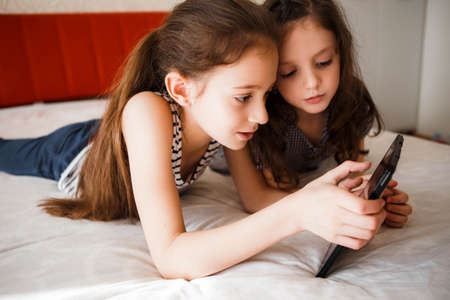 Children using digital gadgets at home. Little girls playing games on the tablet lying on the bed in the bedroom.