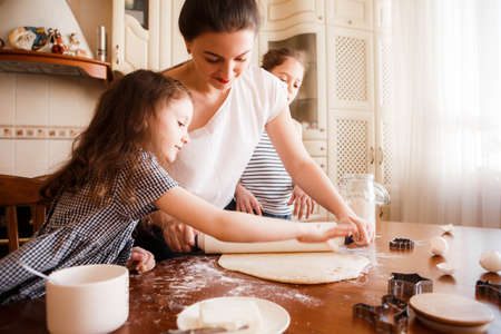 Mom and daughters prepare pastries in the bright classic kitchen. Creative mess on the table. Life style.