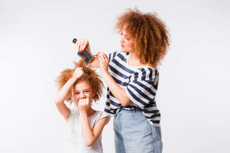 Mom combs her daughters naughty, curly hair.