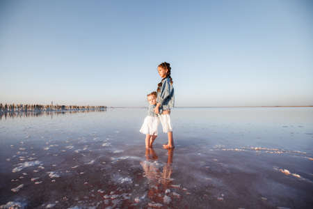 Stylish children in jeans jackets and white dresses on the tide line on the ocean. 写真素材
