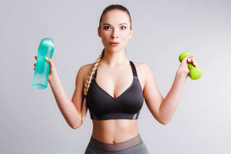 Beautiful athletic girl with a blue shaker on a light gray background.