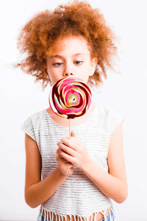Little curly girl with a big lollipop on a light background.
