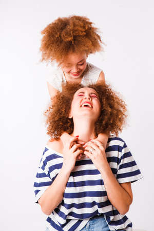 Mom and daughter with natural small curls on the head on a light background. Space for text.