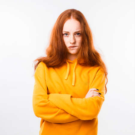 Portrait of an emotional red-haired girl with freckles and braces on a white background. Space for text.