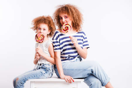 Mom and daughter with natural small curls on the head with bright lollipops, on a light background. Space for text.