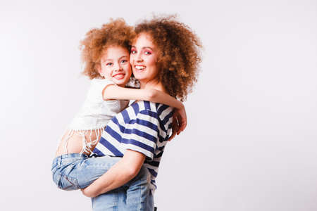 Mom and daughter with natural small curls on the head on a light background.
