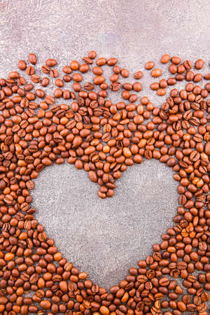 Roasted coffee beans on a grey table Grains of coffee in the shape of a heart on a gray background.