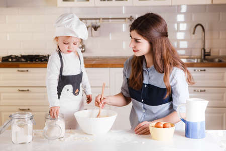 The little daughter in the chefs hat and apron and her mother prepare baking in the bright, classic kitchen. 写真素材