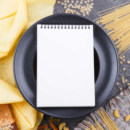open blank notebook with white sheets, raw long paste and ingredients for cooking, top view 写真素材