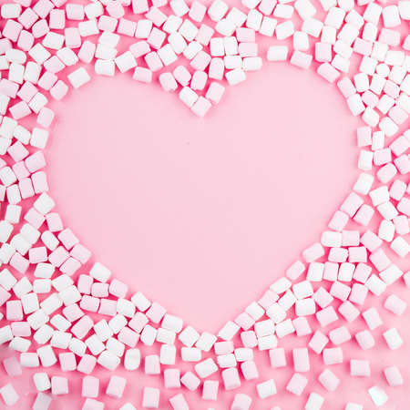 Marshmallows. Background or texture of pink marshmallows. The shape of the heart.