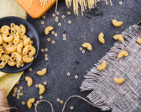 Pasta background. On a black wooden background. Free space for text . Top view