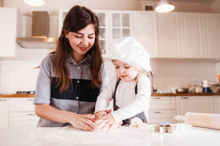 The little daughter in the chefs hat and apron and her mother prepare baking in the bright, classic kitchen. Stock Photo