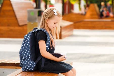Schoolgirl sits on a bench and reads a book.