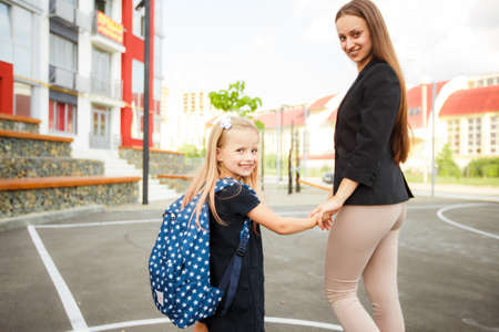 Mama führt ihre Tochter zur Schule. Zur Schule zurückkehren. Frau und Mädchen mit Rucksack hinter dem Rücken. Beginn des Unterrichts. Erster Herbsttag.