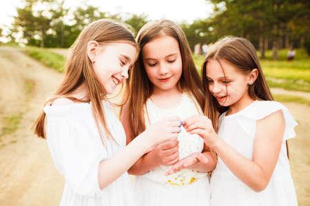 Tres chicas con vestidos blancos caminan en la naturaleza en verano. Pasatiempo infantil durante las vacaciones de verano. Foto de archivo