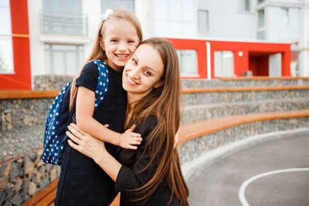 Maman conduit sa fille à l'école. Retour à l'école. Femme et fille avec sac à dos derrière le dos. Début des cours. Premier jour d'automne. Banque d'images