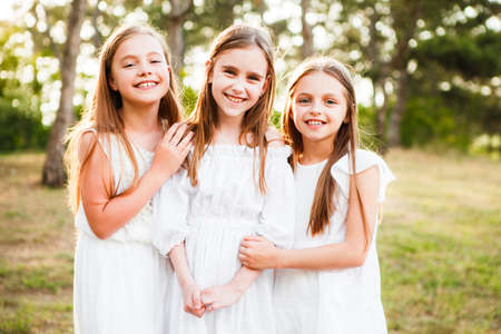 Three girls in white dresses walk in nature in the summer. Childrens pastime during the summer holidays.