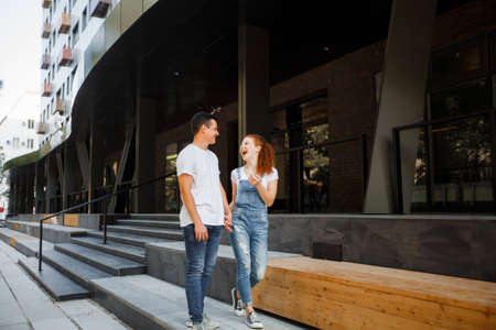 A young couple is walking in the modern city, holding hands. Inspect the conceptual archeology.