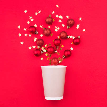 Christmas composition. Coffee glass and christmas red balls on a red background. Holiday concept for a coffee shop.