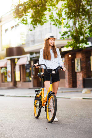 Girl teenager in a hat with a yellow bike walks through the summer city.
