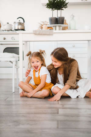Two sisters play in a bright, stylish kitchen. Beautiful interior. Stock Photo