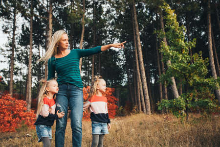 Blonde mother and her twin daughters are walking in the autumn forest among red trees. Zdjęcie Seryjne