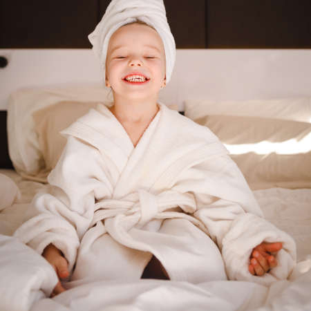 Little girl in a bathrobe and with a turban on her head in a white bed. Foto de archivo
