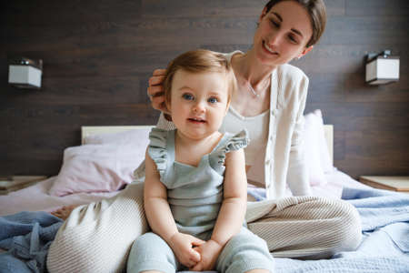 Mom plays with her little daughter in the bedroom. Gentle hugs and fun.
