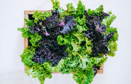 Fresh green and purple kale in a wooden box on a marble background