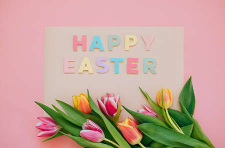 Easter concept. Happy easter paper cut inscription with pink and red tulips on pink background. Copy space, flat lay. Stockfoto