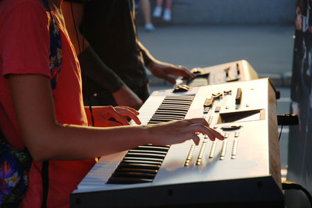 gay girl: Golden hour at sunset gay and girl playing on a synthesizer. Stock Photo