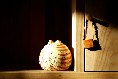 furniture part: cat piggy bank on the shelf in the sun at sunset Stock Photo
