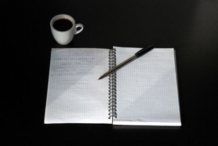wor: Notebook and pen on the black table and cup of coffee.