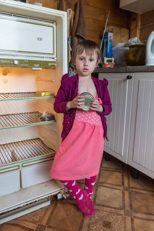 Hungry little girl in old clothes standing next to an empty refrigerator