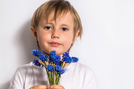 Portrait of the beautiful child holds a bouquet of blue flowers for her mother.