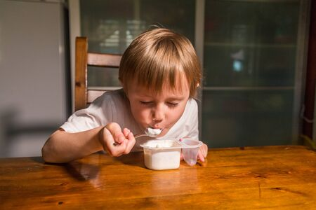 Adorable baby girl eating cottage cheese from spoon, healthy milk snack. Фото со стока