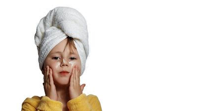 Cute girl in a yellow bathrobewith white cream on her face
