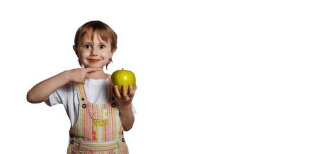Portrait of a little girl pointing to a green apple on white background