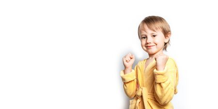Little cute girl in a yellow bathrobe posing funny on a white background. Foto de archivo