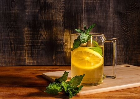 Cup of green tea with lemon and mint on wooden chopping board