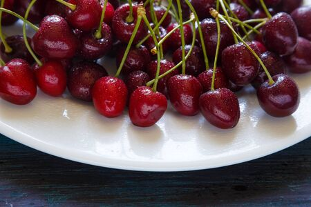 Fresh cherry on plate on wooden blue background.