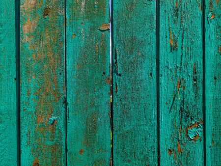 Green wood texture background. .Old ragged painted fence.