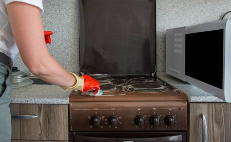 The girl washes an electrical stove in rubber gloves