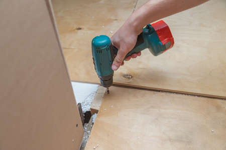 the hand holds a screwdriver and screws the screw into a plywood sheet.